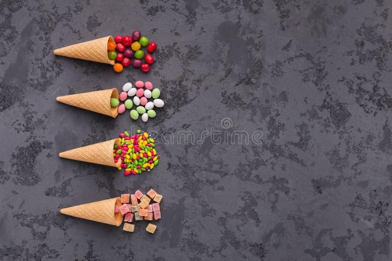 Gofr konusuje z kolorowymi jaskrawymi cukierkami na szarym tle Mieszkanie nieatutowy, odgórny widok obraz stock
