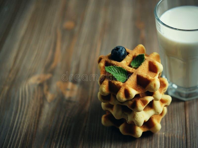 Gofry i szkło z mlekiem Ranku śniadanie na drewnianym tle obraz stock