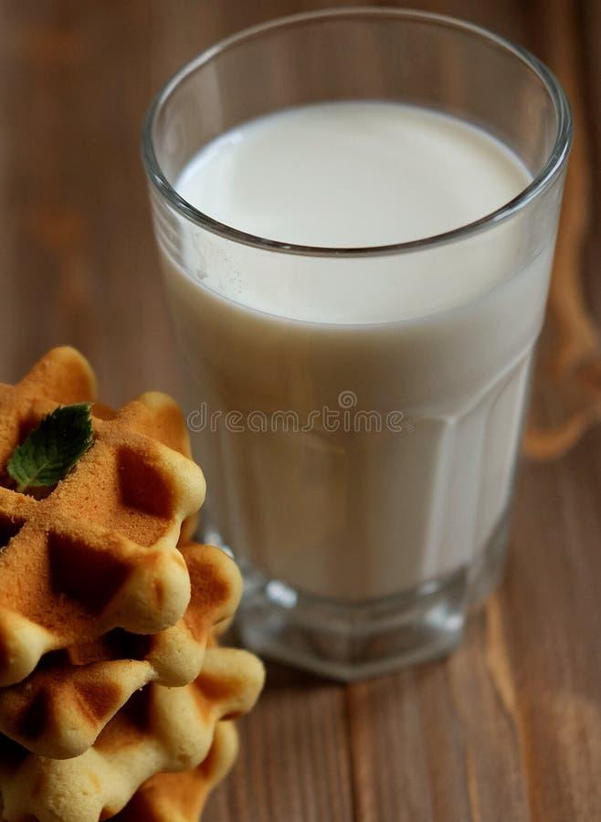 Gofry i szkło z mlekiem Ranku śniadanie na drewnianym tle zdjęcia stock