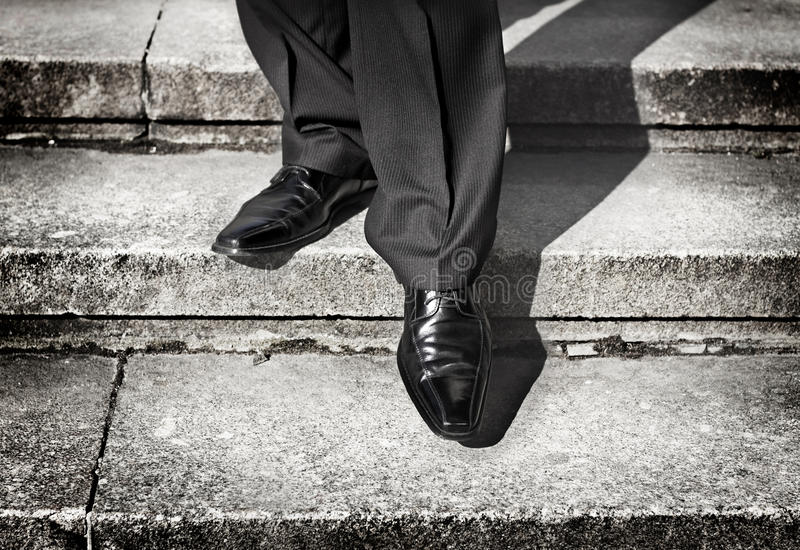 Businessman legs taking step on a lower level on a stairs stock images