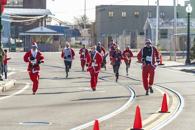 Going for it at Santa Run. New Bedford, Massachusetts, USA - December 8, 2018: Runners heading for finish line on sunny, chilly afternoon at the Santa Sightings stock images