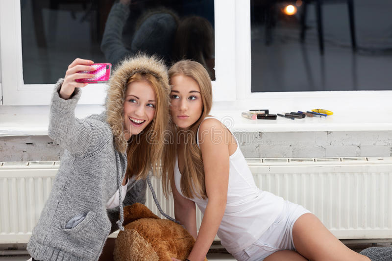 Going social. Two girls are taking picture with mobile phone to publish it in social network stock images
