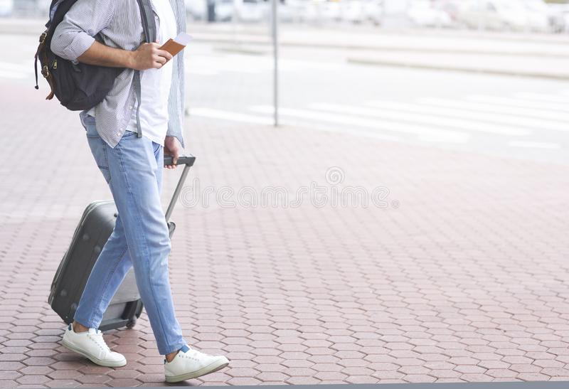 Tourist walking to transportation stop with luggage. Going to bus station. Tourist walking to transportation stop with luggage, empty space royalty free stock photography