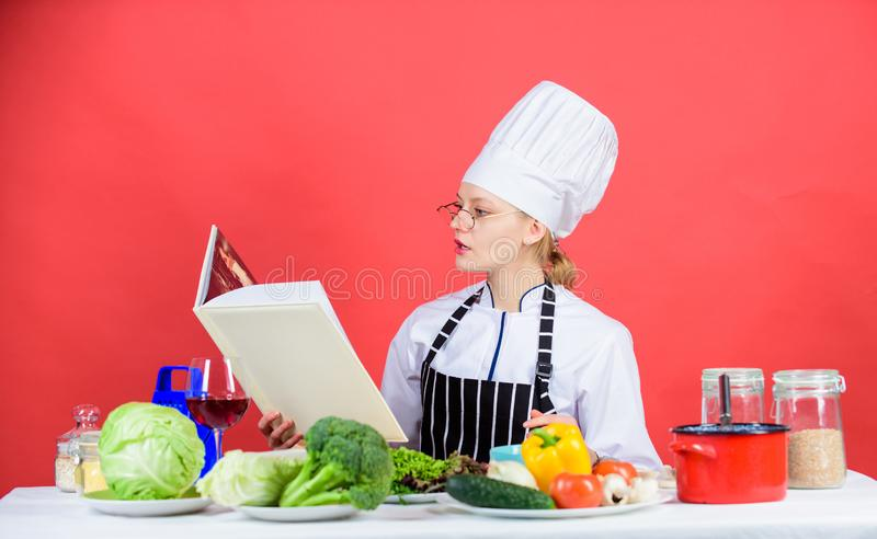 Going to cook something special. Pretty woman reading cook book in kitchen. Lady cook looking for cooking recipe in stock photos