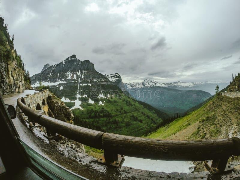Going-to-the-sun Road in de buurt van groene bergen bedekt met sneeuw in het Glacier National Park USA royalty-vrije stock foto