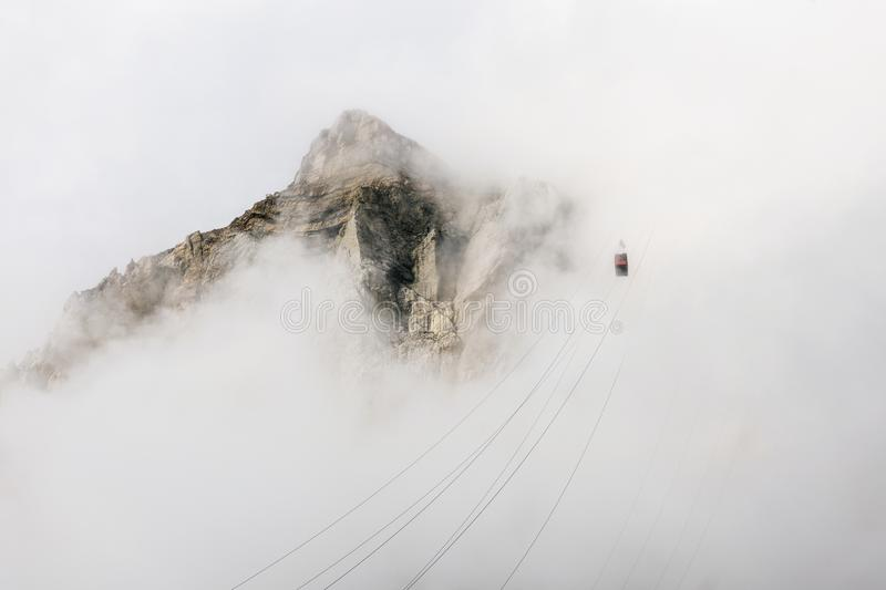 Going up in the fog with cable car stock photography