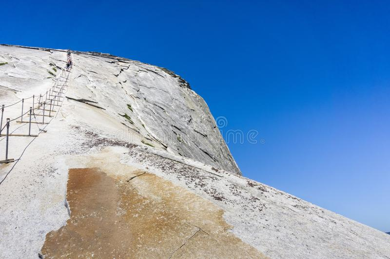 Going up on the Half Dome cables on a sunny summer day, Yosemite National Park, California. Going up on the Half Dome cables on a sunny summer day, blue sky royalty free stock photos