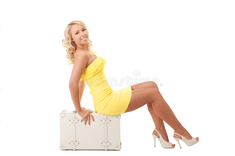 Going for vacations. Young blond girl in yellow dress is sitting on a suitcase almost ready for vacations stock photos