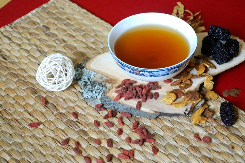 Goji berries, chinese dates, astragalus root pieces with a bowl of herb tea on red background. Side view. Chinese herb tea ingredients. Alternative medicine stock image