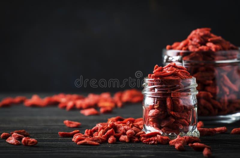 Goji berries in glass jar, dark wooden table, selective focus. Goji berries in glass jar, dark  wooden table, selective focus stock photo
