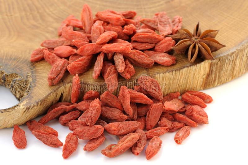Goji berries on oak wood with star anise isolated. Closeup horizontal stock image