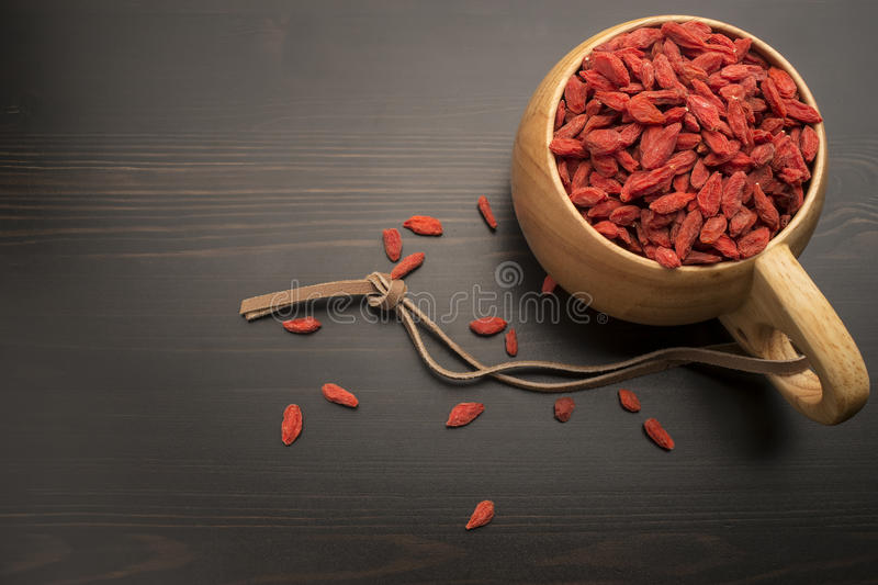 Goji berries in a wooden bowl, around which are scattered on the black berry table. Goji berries in a wooden bowl with suede rope on the handle, which are stock photo