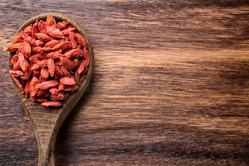 Goji berry. Goji berries on a wooden spoons, wooden brown background stock images