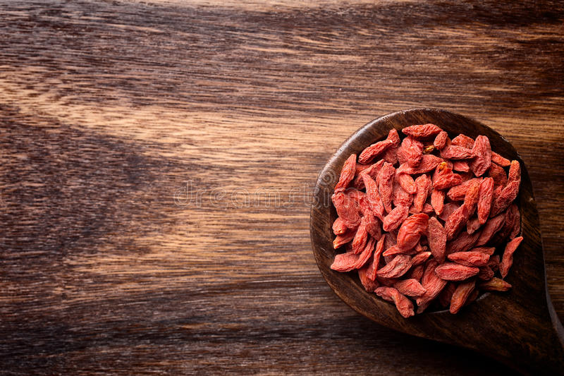 Goji berry. Goji berries on a wooden spoons, wooden brown background stock image