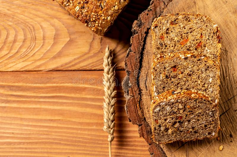Goji berry bread. Sliced rye bread on a wooden stump, with wheat. Whole grain rye bread with seeds, walnut. healthy food concept. Space for text. top view stock image