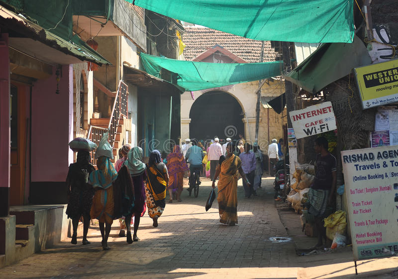 GOKARNA KARNATAKA INDIA - JANUARY 29 2016: Indian woman in yellow traditional indian sari walking down the crowded street in. Gokarna city stock photography