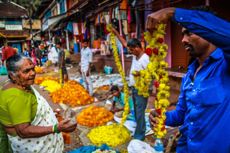 Colors of India. Gokarna Karnataka India November 01, 2017 Portrait of unknown people selling flowers in the street of Gokarna town, in the eveningn royalty free stock images