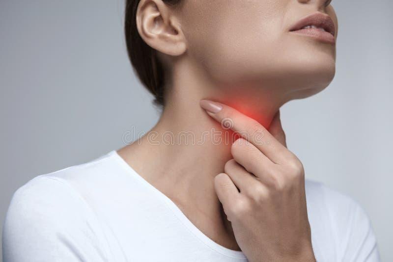 Gola irritata Bei mani e collo della donna del primo piano Dolore della gola immagini stock