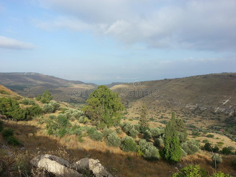 Golan heights with sea of Galilee in the background. Beautiful landscape of rolling hills with browns and greens. The idyllic scene is deceptive. The area is royalty free stock photography