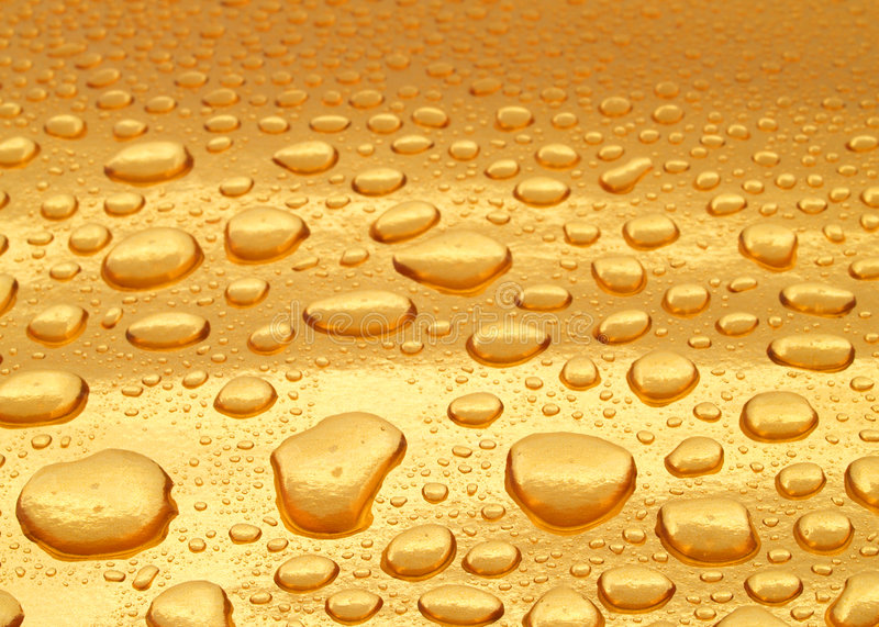 Gold. Liquid gold surface with scattered drops royalty free stock images