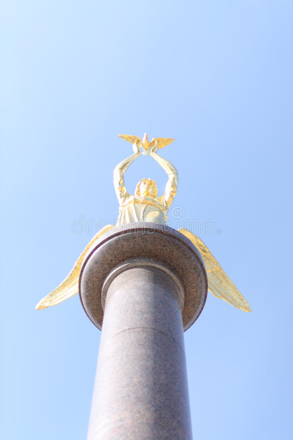 Gold angel. Statue of a gold angel on a granite column royalty free stock image