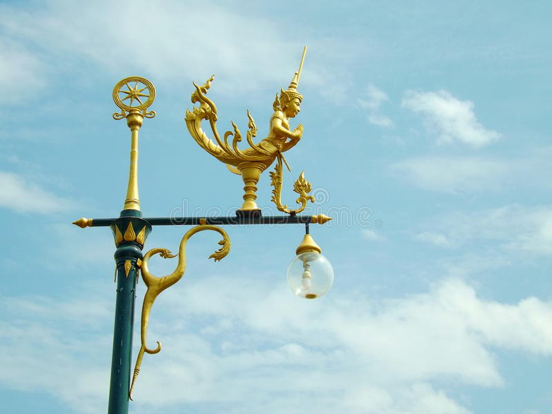 Gold angel on pole. On blue sky stock image