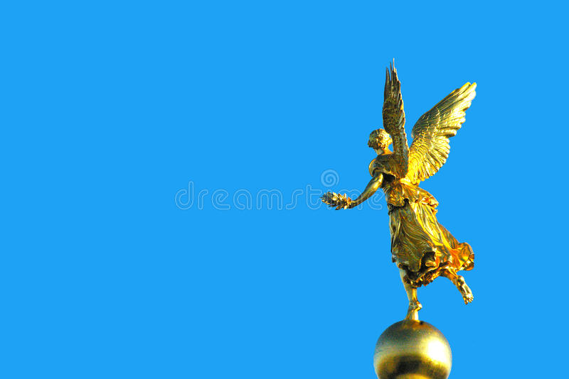 Gold angel statue blue background. Gold angel statue with blue background stock photo