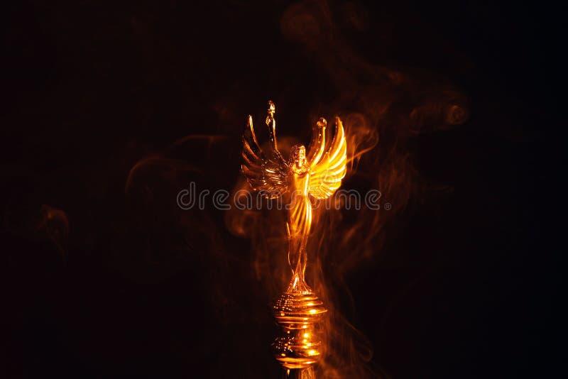 Gold angel statue smoke dark background. Studio stock photo