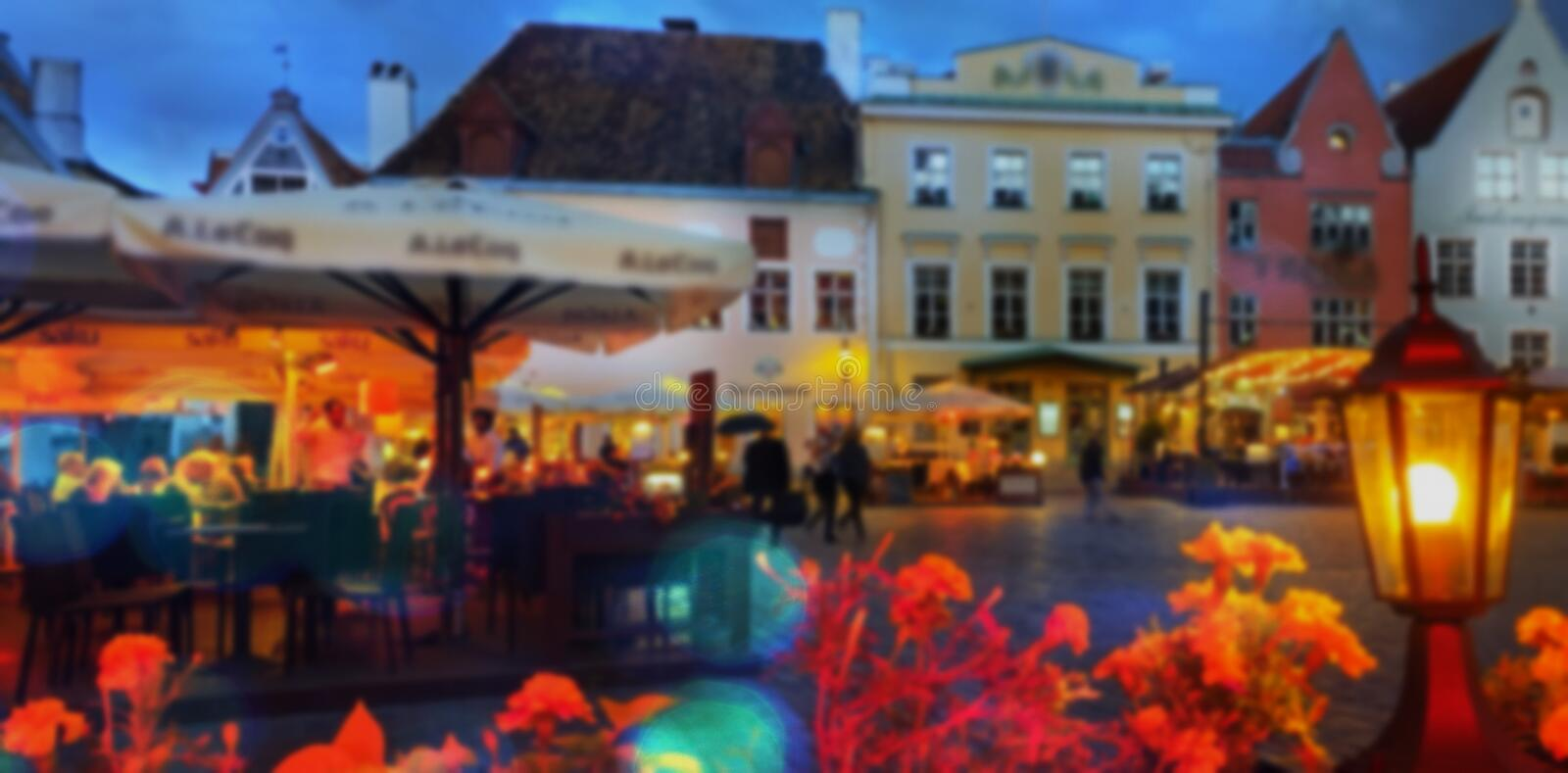 Gold Autumn Rainy evening people umbrellas street cafe city light lamp old town of Tallinn   cityscape travel t royalty free stock photo