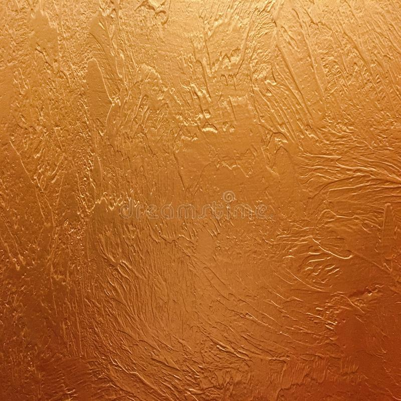 Gold background paper, texture is old vintage distressed solid gold color with rough peeling grunge paint on edges. stock photo