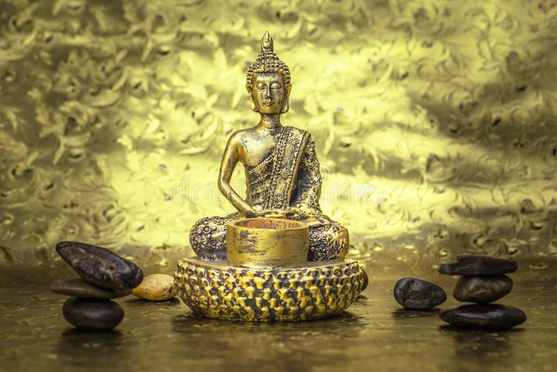 Golden Buddha on the dark gold light bacround. Gold bacround Buddha and stones dark and light colors royalty free stock photo