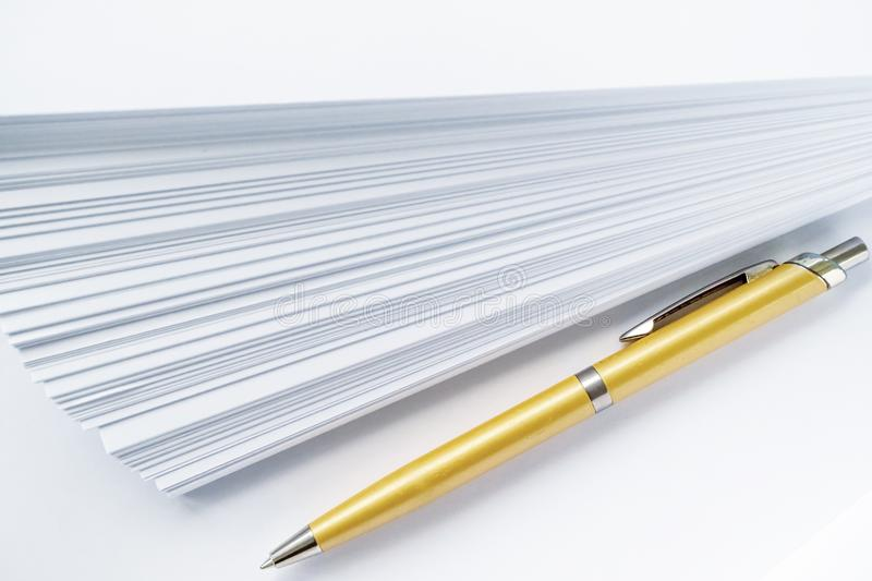 Gold ball point pen lying on the pile of paper for those who write. White background stock photo