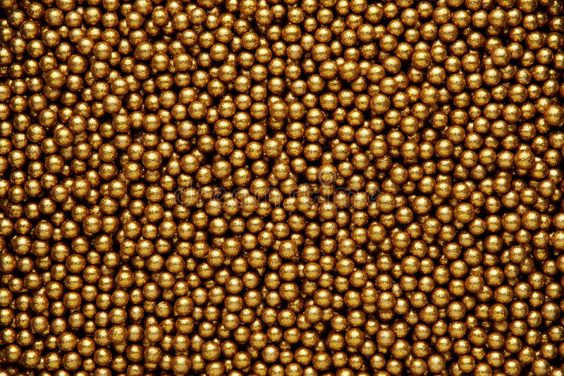 Gold balls background. Decorative festive background of small gold balls with a shiny metallic finish and rough surface texture stock image