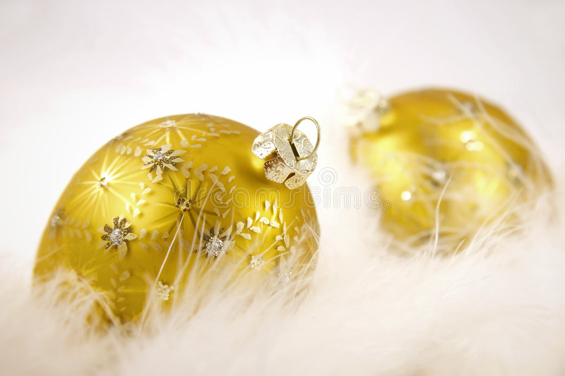 Gold balls with feathers. Gold christmas balls in feathers on isolated white background stock images