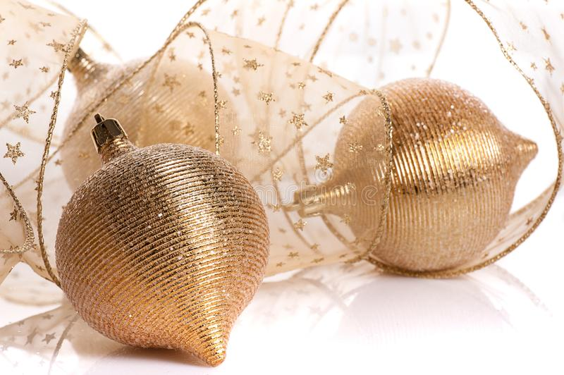 Gold Christmas decoration. Gold balls with transparent golden ribbon on white background royalty free stock image