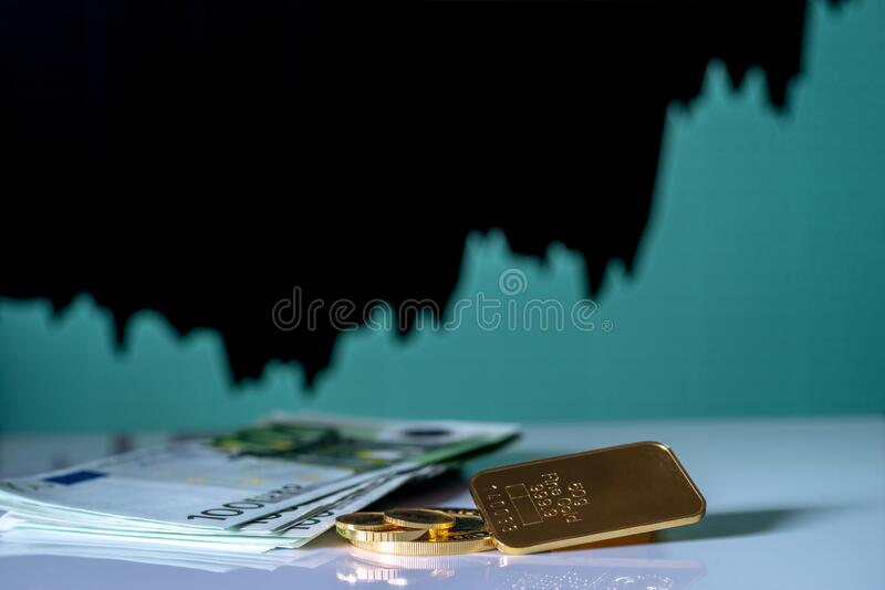 Gold bar, coins and a one hundred euro banknotes on the background of the growth chart. Selective focus royalty free stock photo