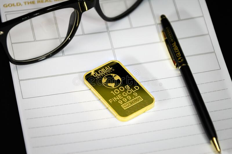 Gold bar with pen and eyeglasses stock photography