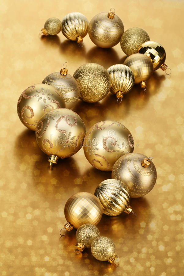 Gold Baubles. Line of Gold Baubles on golden abstract background royalty free stock photos