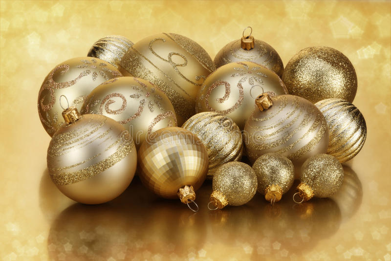 Gold Baubles. Of various sizes and designs on gold bokeh background royalty free stock photo