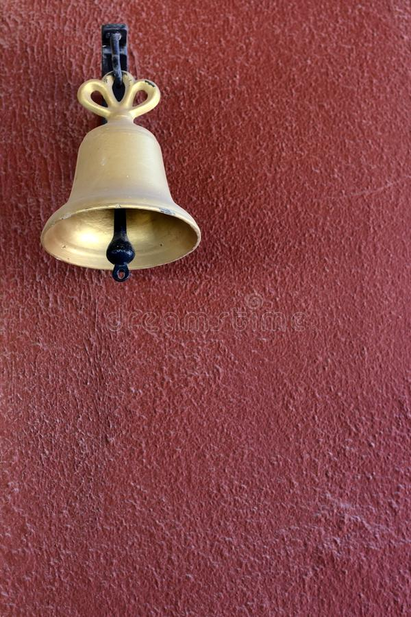 A gold bell on a red painted wall stock image