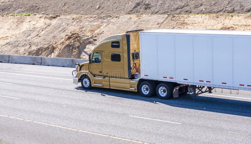 Gold big rig modern semi truck transporting cargo in semi trailer driving on the multiline highway with developed hill land. Gold powerful big rig professional royalty free stock photo
