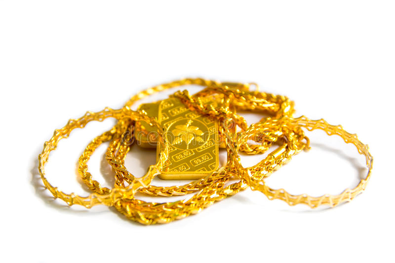 Gold biscuit bar, chains, ornaments on a white background. royalty free stock images