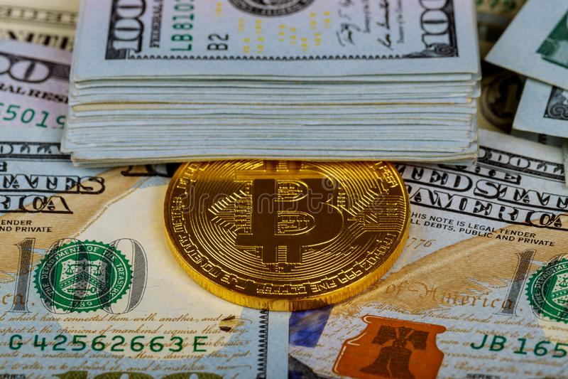 Gold bitcoin coins on one hundred US dollar bills background. Cryptocurrency, New digital currency, Bitcoin exchange to dollar mon stock photo