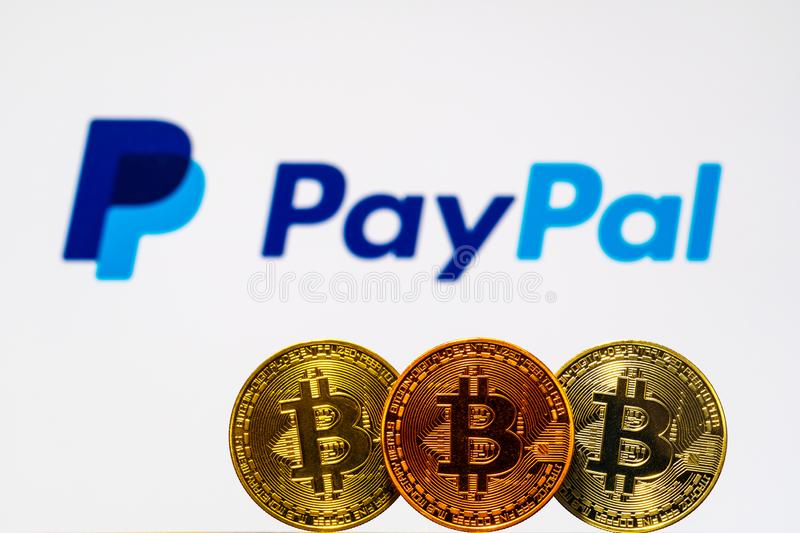 Gold Bitcoin coins with the PayPal logo on background screen. A new type of business finance concept stock photography