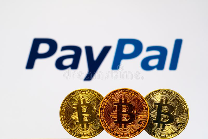 Gold Bitcoin coins with the PayPal logo on background screen. A new type of business finance concept royalty free stock photo