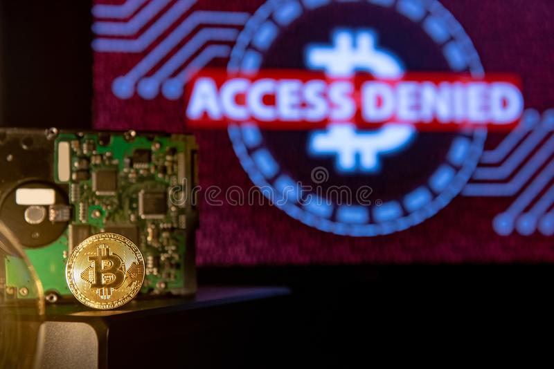 Gold Bitcoin with hard disk, access denied screen in the backgro. Bitcoin gold coin with hard disk drive and red binary screen in the background. Cryptocurrency stock photo