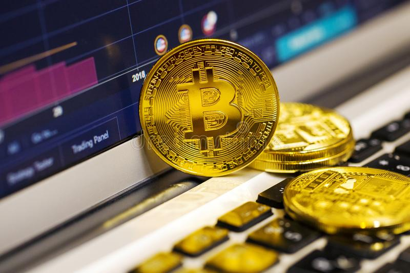 Gold bitcoin on the laptop keyboard on the background of the stock chart. Gold coin bitcoin on the laptop keyboard on the background of the stock chart stock images