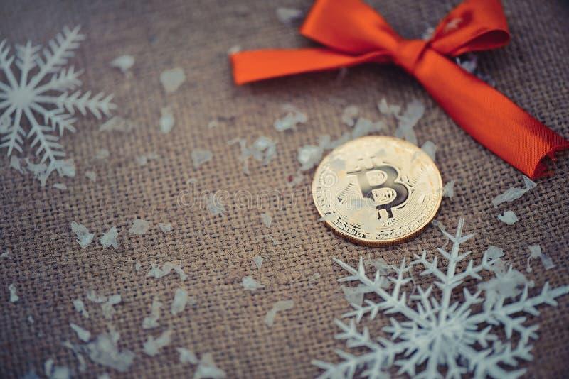 Gold-bitcoin Schlüsselwährung bitcoin auf einem roten Bogen und Schneeflocken des Weihnachtshintergrundes Probleme und Geschäftsw lizenzfreie stockbilder