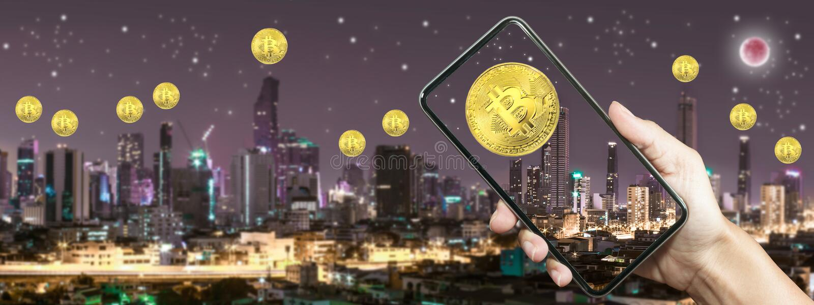 Gold bitcoin on screen smart phone with Building in Bangkok stock photo