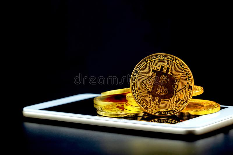 Gold bitcoin on tablet computer isolated on black background, coin money currency virtual digital exchange cash royalty free stock photo